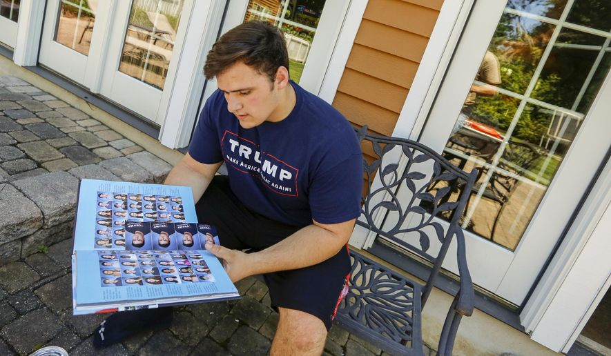 """In this June 9, 2017, file photo, Grant Berardo, a student at Wall High School, flips through his 2017 school yearbook in Wall, N.J. The yearbook includes a photo of him wearing a digitally altered T-shirt that originally included the words """"Trump: Make America Great Again."""" (Andrew Mills/NJ Advance Media via AP, File)"""