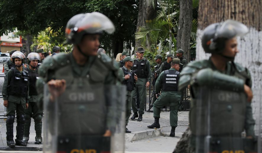 Venezuelan Bolivarian National stand guard around the National Assembly building as the opposition-controlled congress met to discuss a move could provide political cover for greater international involvement in the nation's crisis, in Caracas, Venezuela, Tuesday, May 7, 2019. Military police prevented journalists from entering the National Assembly, and some reporters were harassed by government supporters outside the building. (AP Photo/Fernando Llano)