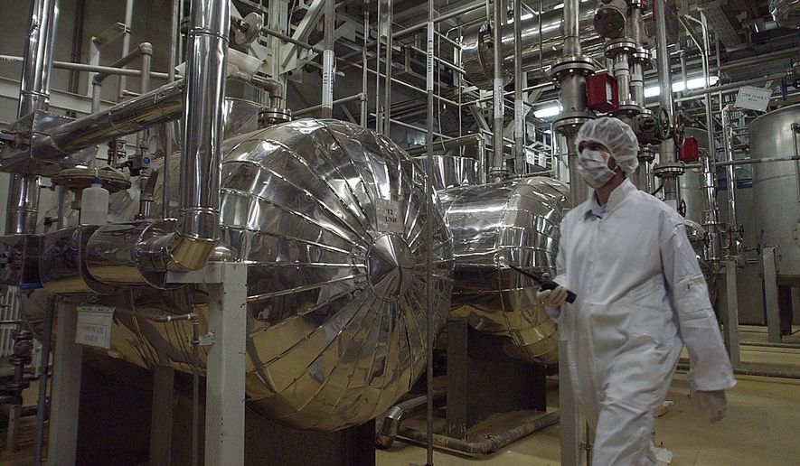 In this March 30, 2005 file photo, an Iranian security official in protective clothing walks through part of the Uranium Conversion Facility just outside the Iranian city of Isfahan. (AP Photo/Vahid Salemi, File) **FILE**
