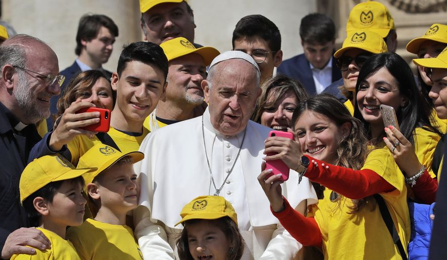 Pope Francis poses for a group photo with youths wearing shirts and holding flags of an association for the protection of abused children, at the end of his weekly general audience, in St. Peter's Square, at the Vatican, Wednesday, May 8, 2019. (AP Photo/Alessandra Tarantino)