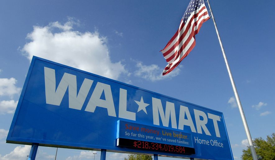 In this Oct. 5, 2007, file photo, an American flag flies in front of the Walmart Stores Inc. headquarters in Bentonville, Ark. Walmart said Wednesday, May 8, 2019, that it will raise the minimum age for tobacco products and e-cigarettes to 21 in an effort to combat tobacco sales to minors. The worlds largest retailer says the new rule will take effect in July, and will also include its Sams Club warehouse stores. (AP Photo/April L. Brown, File) **FILE**