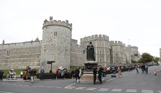 Two police stand by the Queen Victoria statue, outside Windsor Castle in Windsor, south England, Monday May 6, 2019, after Prince Harry announced that his wife Meghan, Duchess of Sussex, has given birth to a boy. (AP Photo/Alastair Grant)