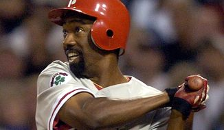 FILE - In this Aug. 4, 2004, file photo, Philadelphia Phillies' Doug Glanville follows through on an RBI triple hit off San Diego Padres pitcher Adam Eaton during the third inning in San Diego. The Chicago Cubs say they're investigating a fan using what appeared to be an offensive hand gesture associated with racism behind Glanville, now a television reporter, who was on the air for NBC Sports Chicago. (AP Photo/Denis Poroy, File)
