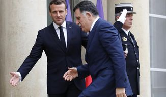 French President Emmanuel Macron, right, welcomes Libyan Prime Minister Fayez Sarraj Wednesday, May 8, 2019 at the Elysee Palace in Paris. Sarraj met Italian Prime Minister Giuseppe Conte Tuesday in Rome. (AP Photo/Christophe Ena)