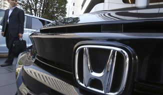 A visitor looks at a car displayed at the showroom at the Honda Motor Co. headquarters in Tokyo, Wednesday, May 8, 2019. Honda reported a loss for January-March, despite growing sales, as an unfavorable exchange rate, income tax expenses and other costs hurt results. (AP Photo/Koji Sasahara)