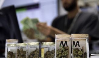 In this July 1, 2017 file photo, a cashier rings up a marijuana sale at the Essence cannabis dispensary in Las Vegas. (AP Photo/John Locher, File)