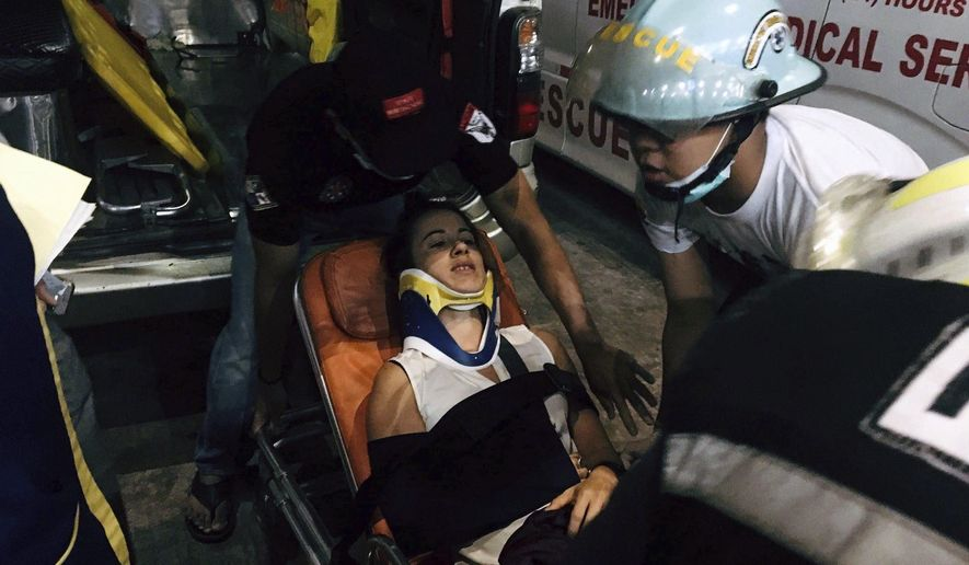Myanmar rescue members help an injured passenger in Yangon International airport, Wednesday, May 8, 2019, in Yangon, Myanmar. A plane operated by Biman Bangladesh Airlines skidded off the runway while landing Wednesday evening at Myanmar's Yangon International Airport, injuring at least four people including a pilot, an airline official said. Biman spokesman Shakil Meraj said the accident occurred when the Bombardier Dash-8 Q400 aircraft was landing in bad weather after a flight from Bangladesh's capital, Dhaka. (AP Photo/Aye Win Myint)