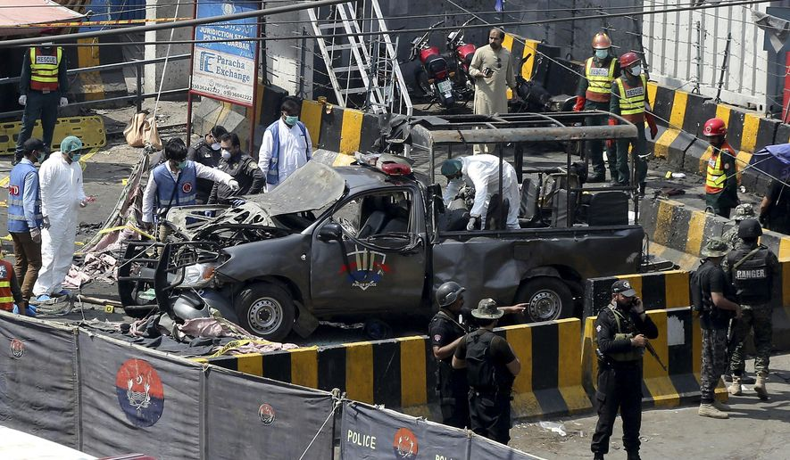 Pakistani security personnel surround a damaged police van in Lahore, Pakistan, Wednesday, May 8, 2019. A powerful bomb exploded near security forces guarding a famous Sufi shrine in Pakistan on Wednesday, police said. (AP Photo/K.M. Chaudary)
