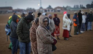South Africans queue in the early morning cold to cast their votes in the mining settlement of Bekkersdal, west of Johannesburg, in South Africa Wednesday, May 8, 2019. South Africans are voting Wednesday in a national election that pits President Cyril Ramaphosa's ruling African National Congress against top opposition parties Democratic Alliance and Economic Freedom Fighters, 25 years after the end of apartheid. (AP Photo/Ben Curtis)