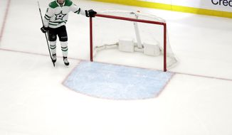 Dallas Stars' Miro Heiskanen, of Finland, stands at the net as the St. Louis Blues celebrate after Pat Maroon scored during the second overtime in Game 7 of an NHL second-round hockey playoff series Tuesday, May 7, 2019, in St. Louis. The Blues won 2-1, taking the series. (AP Photo/Jeff Roberson)