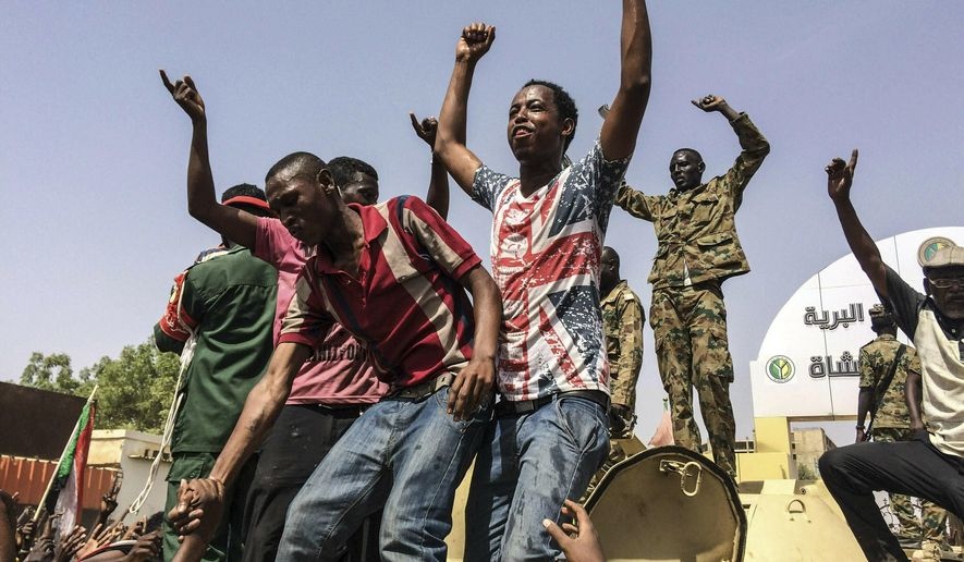 FILE - In this April 11, 2019  file photo, Sudanese celebrate after officials said the military had forced longtime autocratic President Omar al-Bashir to step down after 30 years in power in Khartoum, Sudan. As the uprising against Sudanese President Omar al-Bashir gained strength, Egypt, the United Arab Emirates and Saudi Arabia began reaching out to the military through secret channels to encourage his removal from power. They had long viewed al-Bashir as a problem because of his close ties to Islamists. (AP Photo, File)