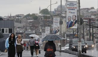 People walk on Galata Bridge over the Golden Horn in Istanbul, decorated with electoral posters of Turkey's President Recep Tayyip Erdogan and his party's Istanbul mayoral candidate Binali Yildirim, Tuesday, May 7, 2019. Ruling in favor of Erdogan's governing party, Turkey's top electoral body on Monday annulled the results of the March 31 vote in Istanbul which the opposition candidate Ekrem Imamoglu narrowly won and scheduled a re-run for June 23.Erdogan insisted Tuesday that the repeat of the mayoral race in Istanbul will strengthen democracy and lift the shadow that was cast over the vote.(AP Photo/Lefteris Pitarakis)