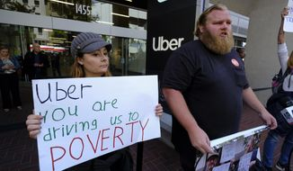 Annette Ribero, left, of San Jose, and Jeff Terry, of Sacramento, hold signs during a demonstration outside of Uber headquarters Wednesday, May 8, 2019, in San Francisco. As Uber executives lure investors to infuse the company with billions of dollars ahead of the largest technology IPO this year, the men and women behind the wheels of the largest ride-hailing companies are pushing for higher wages and recognition for their role in building the companies. (AP Photo/Eric Risberg)