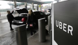In this March 15, 2017, file photo, a sign marks a pick-up point for the Uber car service at LaGuardia Airport in New York. Drivers for ride-hailing giants Uber and Lyft are planning to turn off their apps to protest what they say are declining wages at a time when both companies are raking in billions of dollars from investors. (AP Photo/Seth Wenig, File)