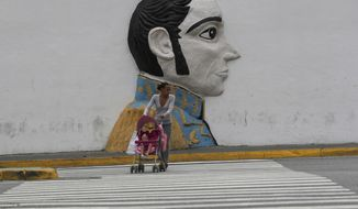 """A pedestrian looks to cross an avenue backdropped by a wall relief of Venezuelan hero Simon Bolivar, just outside of the Supreme Court building, in Caracas, Venezuela, Wednesday, May 8, 2019. Supreme Court Justice Moreno spoke Wednesday following U.S. Vice President Mike Pence's remarks that the U.S. would extend sanctions to all members of the Venezuelan court if they continue to be a """"political tool"""" of President Nicolás Maduro. (AP Photo/Martin Mejia)"""