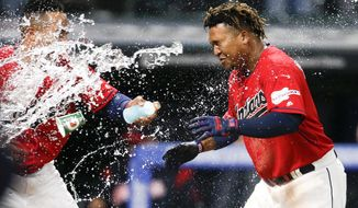 Cleveland Indians' Jose Ramirez, right, is greeted at home plate by Leonys Martin after hitting a game-winning two-run home run off Chicago White Sox relief pitcher Kelvin Herrera during the ninth inning of a baseball game Wednesday, May 8, 2019, in Cleveland. The Indians defeated the White Sox 5-3. (AP Photo/Ron Schwane)