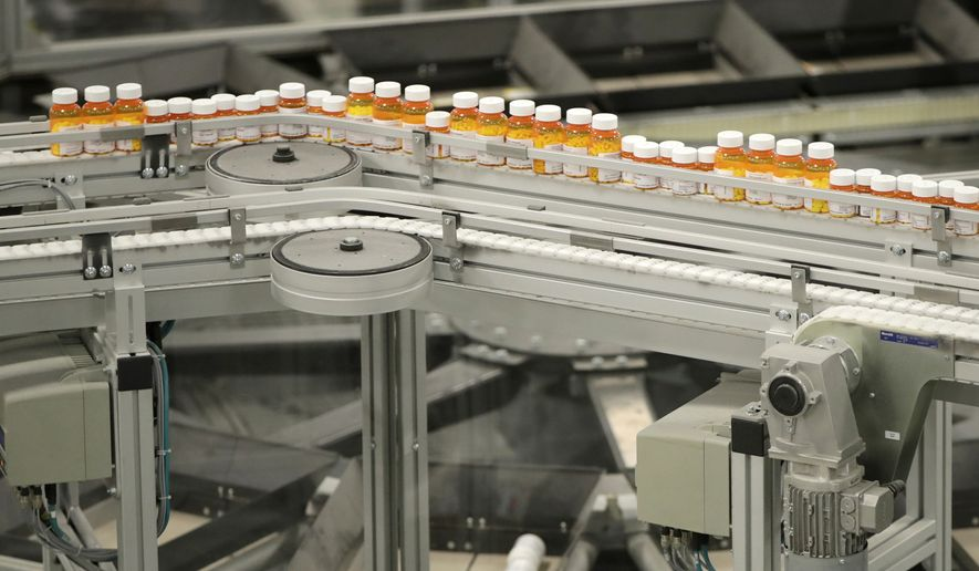 In this July 10, 2018 file photo, bottles of prescription medicines ride on a conveyor belt at a pharmacy warehouse in Florence, N.J.  (AP Photo/Julio Cortez, File) **FILE**