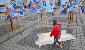 A child walks by boards depicting the creation of the Bucharest EU Children Declaration, a call for EU leaders to make child participation a priority, by children supported by UNICEF in the Piata Mare square in the Transylvanian town of Sibiu, Romania, Wednesday, May 8, 2019. European Union leaders hold an EU summit in Sibiu on Thursday to start setting out a course for increased political cooperation in the wake of the impending departure of the United Kingdom from the bloc. (AP Photo/Vadim Ghirda)
