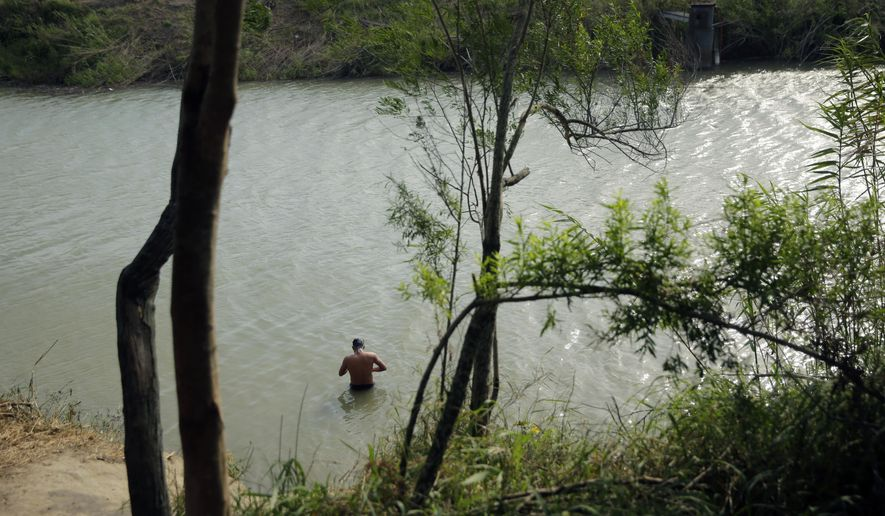 In this April 30, 2019, photo, a migrant who is seeking asylum in the United States bathes in the Rio Grande River near an encampment in Matamoros, Mexico. People waiting at a nearby encampment sometimes climb into the Rio Grande to wash up. (AP Photo/Eric Gay) **FILE**