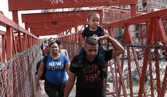 In this April 29, 2019, photo, Cuban migrants are escorted in Ciudad Juarez, Mexico, by Mexican immigration officials as they cross the Paso del Norte International bridge to be processed as asylum seekers on the U.S. side of the border. U.S. authorities have been telling asylum seekers that they are at capacity and to return when space opens up, a hands-off approach that has created haphazard and often-dubious arrangements in Mexico.  (AP Photo/Christian Torres)
