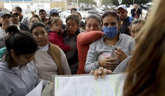 FILE - In this Oct. 23, 2018, file photo, women in Tijuana, Mexico, look on as numbers and names are called to from a list of asylum seekers who want to cross the border into the United States, Tijuana is the busiest border crossing, with about 70,000 people crossing each way every day in cars and about 40,000 on foot. (AP Photo/Gregory Bull, File)