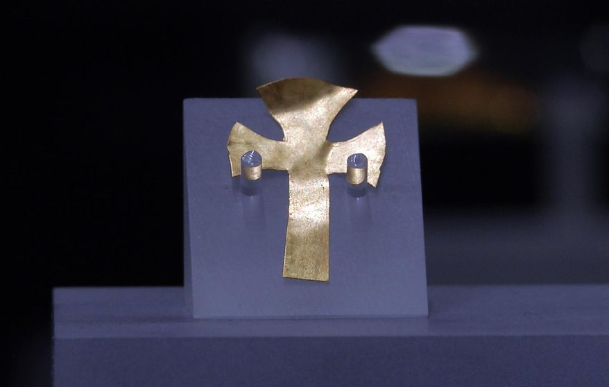 A gold foil cross uncovered at an Anglo-Saxon burial site in the village of Prittlewell in 2003 on display at Southend Central Museum in Southend, England, Thursday, May 8, 2019. Archaeologists say an underground chamber discovered accidentally by road workers may be the site of the earliest Christian royal burial in Britain. The chamber uncovered between a road and a railway line in the village of Prittlewell in 2003 turned out to be a 1,400-year-old burial site. (AP Photo/James Brooks)