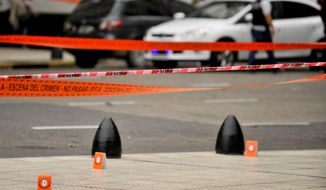 CORRECTS TO CHANGE FROM MOVING VEHICLE TO PARKED CAR - Evidence tent markers mark the crime scene where Argentine lawmaker Hector Olivares was seriously injured and another man was killed after they were shot at from a parked car near the Congress building in Buenos Aires, Argentina, Thursday, May 9, 2019. Officials say Olivares was shot at around 7 a.m. local time. Olivares is a representative of La Rioja province in Argentina's lower house of Congress. He is being treated at a hospital in Buenos Aires. (AP Photo/Natacha Pisarenko)