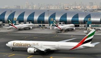 FILE - In this March 22, 2017, file photo, an Emirates plane taxis to a gate at Dubai International Airport in Dubai, United Arab Emirates. The Middle East's biggest airline, Emirates, said Thursday, May 9, 2019, that profits were down almost 70% in the past fiscal year reaching lows of $237 million compared to last year's $762 million. (AP Photo/Adam Schreck, File)