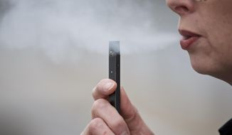 FILE - In this April 16, 2019, file photo, a woman exhales a puff of vapor from a Juul pen in Vancouver, Wash. Under intense scrutiny amid a wave of underage vaping, Juul is pushing into television with a multimillion-dollar campaign rebranding itself as a stop-smoking aid for adults trying to kick cigarettes. (AP Photo/Craig Mitchelldyer, File)