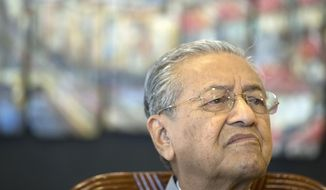 Malaysian Prime Minister Mahathir Mohamad listens to questions during an interview with foreign media on one years anniversary of government in Putrajaya, Malaysia, Thursday, May 9, 2019. Mahathir reiterates that he is an interim prime minister and will stick to his promise to hand over to his successor Anwar Ibrahim. (AP Photo/Vincent Thian)