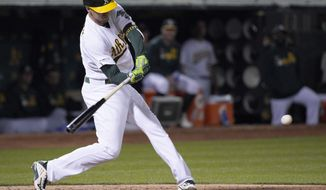Oakland Athletics' Stephen Piscotty hits a single to drive in two runs against the Cincinnati Reds during the fifth inning of a baseball game Wednesday, May 8, 2019, in Oakland, Calif. (AP Photo/Tony Avelar)