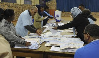 In this photo taken Wednesday, May 8, 2019, vote counting begins at a polling station in Cape Town, South Africa. Vote counting continued Thursday May 9, 2019 after South Africans voted Wednesday in a national election that pits President Cyril Ramaphosa's ruling African National Congress against top opposition parties Democratic Alliance and Economic Freedom Fighters, 25 years after the end of apartheid. (AP Photo/Nasief Manie)