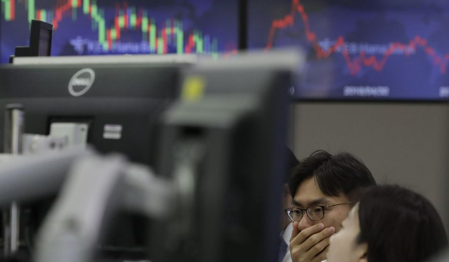 Currency traders watch the computer monitors near the screen showing the foreign exchange rate at the foreign exchange dealing room in Seoul, South Korea, Thursday, May 9, 2019. Asian shares were mostly lower Thursday amid investor jitters ahead of the latest round of trade talks between the U.S. and China. (AP Photo/Lee Jin-man)