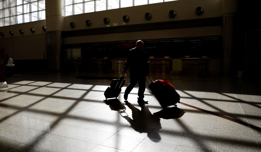 FILE- In this Nov. 22, 2018, file photo a traveler wheels his luggage through Hartsfield-Jackson Atlanta International Airport on Thanksgiving in Atlanta. The latest round of China tariff hikes, which went into effect Friday, May 10, 2019. will hit a range of consumer goods, including luggage, furniture and seafood. (AP Photo/David Goldman, File)