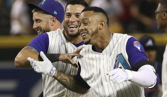 Arizona Diamondbacks' Ketel Marte, right, celebrates his walk-off single against the Atlanta Braves in the 10th inning with David Peralta, middle, and Merrill Kelly, left, in a baseball game Thursday, May 9, 2019, in Phoenix. The Diamondbacks won 3-2. (AP Photo/Ross D. Franklin)