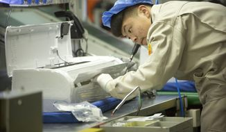 In this Feb. 24, 2017, photo, a factory worker assembles the case of an air conditioner on an assembly line at a Haier factory in Jiaozhou near Qingdao in eastern China's Shandong Province. U.S. President Donald Trump's latest tariff hike on Chinese goods took effect Friday, May 10, 2019, and Beijing said it would retaliate, escalating a battle over China's technology ambitions and other trade tensions. (AP Photo/Mark Schiefelbein)