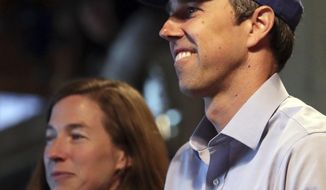 Democratic presidential candidate and former Texas Congressman Beto O'Rourke smiles as he stands with his wife Amy while being introduced at Colby-Sawyer College in New London, N.H., Friday, May 10, 2019. (AP Photo/Charles Krupa)