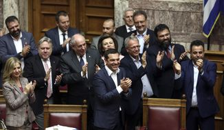 Greece's Prime Minister Alexis Tsipras, center, and his lawmakers applaud after a parliamentary session where the government won a confidence vote, in Athens, on Friday, May 10, 2019. Greek lawmakers were holding a vote of confidence in the left-wing government, after Prime Minister Alexis Tsipras turned a censure motion against a junior minister into a test of his entire administration. (AP Photo/Yorgos Karahalis)