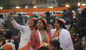 Congress party supporters take selfies during an election campaign rally in New Delhi, India, Thursday, May 9, 2019. In total, some 900 million people are registered to vote for candidates to fill 543 seats in India's lower house of Parliament. Voting concludes on May 19 and counting is scheduled for May 23. (AP Photo/Manish Swarup)