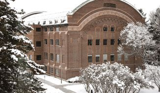 FILE - In this Jan. 23, 2019, file photo, snowfall surrounds Romney Hall on the campus of Montana State University in Bozeman, Mont. Gov. Steve Bullock signed a series of bills Friday, May 10, 2019, to authorize spending of nearly $400 million on infrastructure projects in the state, including $25 million to renovate Romney Hall and add more classrooms. (Rachel Leathe/Bozeman Daily Chronicle via AP, File)