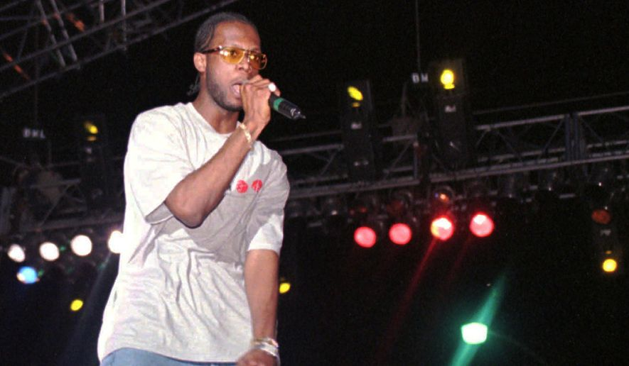 "In this April 12, 1997, file photo, Prakazrel ""Pras"" Michel, part of the group the Fugees, sings on stage during a concert in Port-au-Prince, Haiti. A lawyer for one of the founding members of the 1990s hip hop group the Fugees says his client is facing charges related to 2012 campaign contributions. Defense lawyer Barry Pollack said Friday, May 10, 2019, that Michel is innocent and looks forward to having the case heard by a jury.(AP Photo/Daniel Morel, File)"