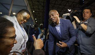 Mmusi Maimane, leader of the largest opposition party, the Democratic Alliance, is greeted by a supporter as he visits the Independent Electoral Commission Results Center in Pretoria, South Africa Thursday, May 9, 2019. South Africans voted Wednesday in a national election and preliminary results show that the ruling African National Congress party (ANC) has an early lead in the national elections but has seen its share of the vote drop significantly. (AP Photo/Ben Curtis)