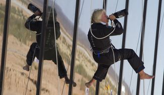 FILE - In this Oct. 17, 2011 file photo British billionaire Sir Richard Branson drinks champagne after repelling down the side of the new Spaceport America hangar in Upham, N.M. Branson is taking another concrete step toward offering rides into the close reaches of space for paying passengers. Branson announced Friday, May 10, 2019, that Virgin Galactic will immediately begin shifting operations from California to the spaceport and specialized runway in the New Mexico desert in final preparations for commercial flights. He says Virgin Galactic's development and testing program has advanced enough to make the move, which will continue through the summer. (AP Photo/Matt York, File)