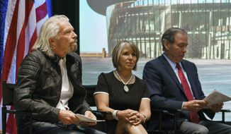 Virgin Galactic founder Richard Branson, left, New Mexico Gov. Michelle Lujan Grisham and U.S. Sen. Tom Udall wait to speak during an event at the state capital on Friday, May 10, 2019, in Santa Fe, N.M.  Branson announced Friday that his company will begin shifting operations from California to a spaceport and specialized runway in the New Mexico desert in final preparations for commercial flights.  (AP Photo/Craig Fritz) ** FILE **