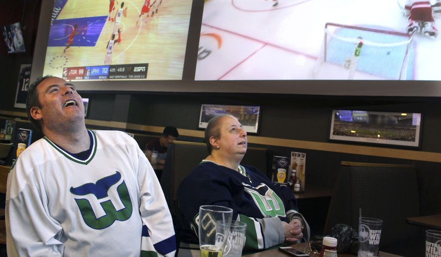 Hartford Whaler Booster club members Matthew Greene, left, and Joanne Coressa watch Game 1 of the NHL Eastern Conference playoff series on Thursday, May 9, 2019, at a restaurant in Manchester, Conn., between the Carolina Hurricanes, the franchise that moved from Hartford 22 years ago, and the Boston Bruins. (AP Photo/Pat Eaton-Robb)