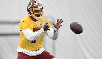 Washington Redskins quarterback Dwayne Haskins takes the snap during an NFL football rookie camp, Saturday, May 11, 2019, in Ashburn, Va. (AP Photo/Nick Wass)