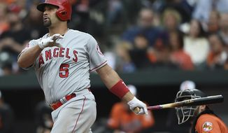 Los Angeles Angels' Albert Pujols follows through on a solo home run against the Baltimore Orioles in the fourth inning of a baseball game Saturday, May 11, 2019, in Baltimore. (AP Photo/Gail Burton)