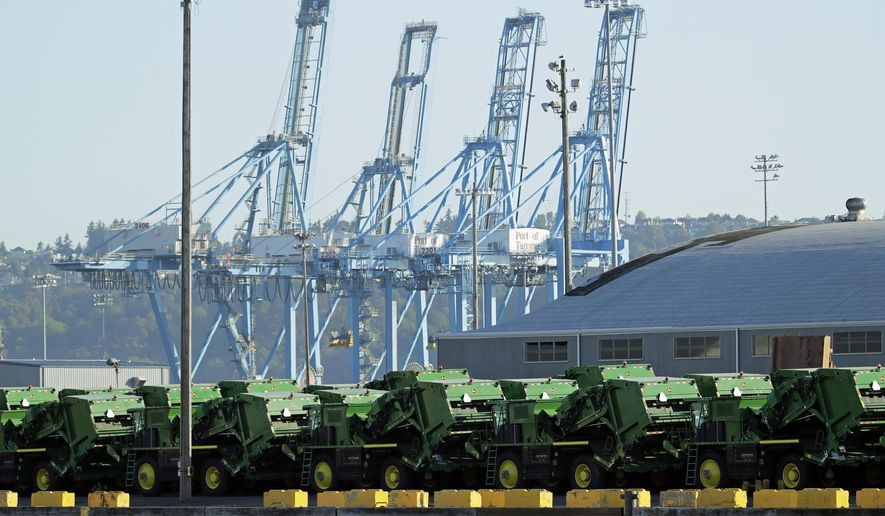 John Deere Agricultural machinery made by Deere & Company sits staged for transport, Friday, May 10, 2019, near cranes at the Port of Tacoma in Tacoma, Wash. U.S. and Chinese negotiators resumed trade talks Friday under increasing pressure after President Donald Trump raised tariffs on $200 billion in Chinese goods and Beijing promised to retaliate. (AP Photo/Ted S. Warren)