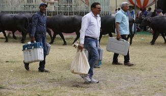 Election officers carry electronic voting machines before proceeding towards their allotted polling stations on the eve of polling in Prayagraj, India, Saturday, May 11, 2019. The sixth phase of the seven-phased general elections will be held Sunday. (AP Photo/Rajesh Kumar Singh)