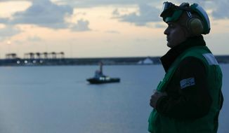 """In this Thursday, May 9, 2019 photo released by the U.S. Navy, Aviation Maintenance Administrationman 2nd Class Jason Caldwell, assigned to the """"Jolly Rogers"""" of Strike Fighter Squadron 103, observes sunrise on the flight deck of the Nimitz-class aircraft carrier USS Abraham Lincoln while transiting the Suez Canal in Egypt. The aircraft carrier and its strike group are deploying to the Persian Gulf on orders from the White House to respond to an unspecified threat from Iran. (Mass Communication Specialist 3rd Class Amber Smalley, U.S. Navy via AP)"""